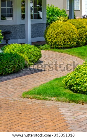 House entrance with paved doorway and nicely trimmed and landscaped front yard  in the suburbs of Vancouver, Canada. Vertical. - stock photo
