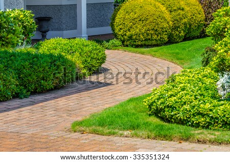 House entrance with paved doorway and nicely trimmed and landscaped front yard  in the suburbs of Vancouver, Canada. - stock photo