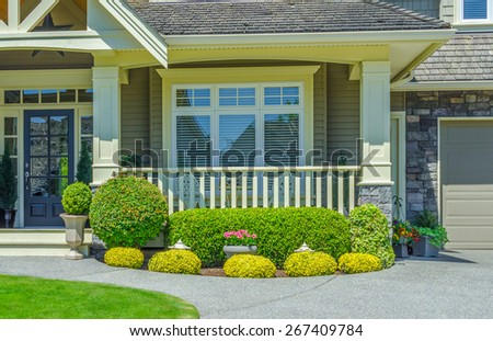House entrance with porch and nicely trimmed and landscaped front yard. - stock photo