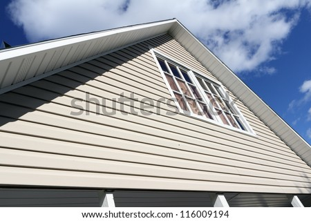 House exterior, against a blue sky. Roof close-up. Low angle view.