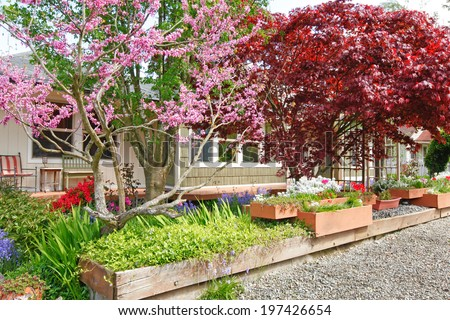 House exterior. Entrance porch with flower bed with blooming flowers and trees - stock photo