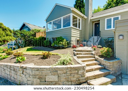 House exterior in clapboard siding and  front yard landscape, Stairs with stone trim - stock photo