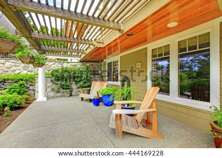 House exterior. View of cozy covered walkout deck with adirondack wooden chairs and concrete floor.