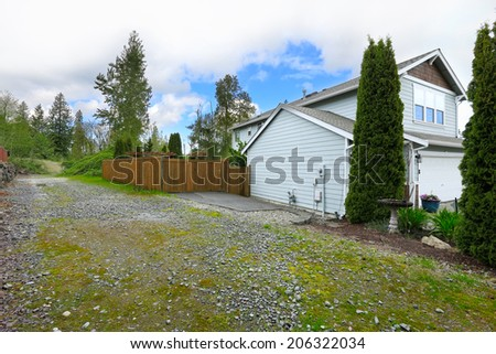 House exterior. View of driveway and fenced backyard