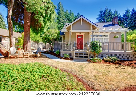 House exterior. View of entrance deck with red door and front yard with outdoor rest area - stock photo