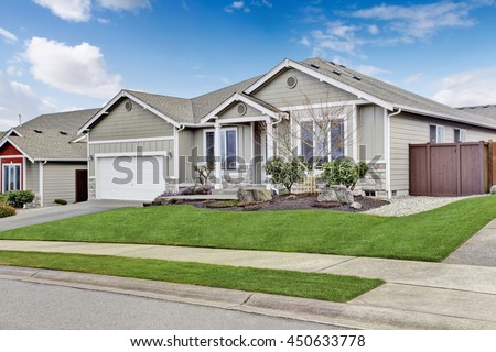 House exterior. View of entrance porch with walkway and garage with driveway - stock photo