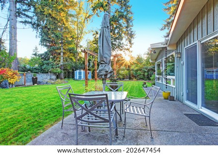 House exterior. View of patio table set with glass top table with chairs and umbrella - stock photo