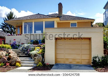 House exterior with large garage and staircase. - stock photo