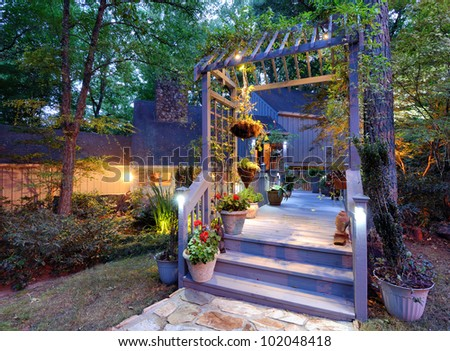 House exterior with porch walkway and lighting in the woods - stock photo