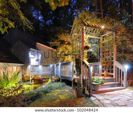 House exterior with porch walkway over a pond and lighting in the woods