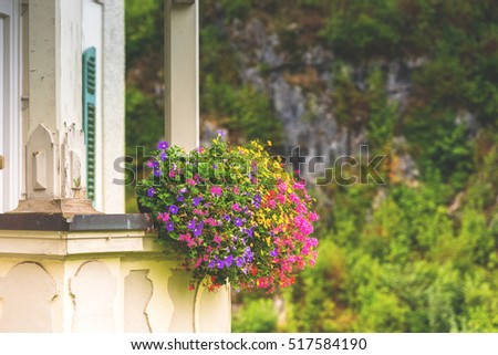 House facade with balcony and flowers. Horizontal shot with a selective focus