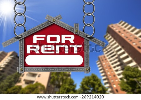 House For Rent Sign - Metallic Meter. Grey metallic meter ruler in the shape of house with text for rent. For rent real estate sign with tall and blurred buildings in the background