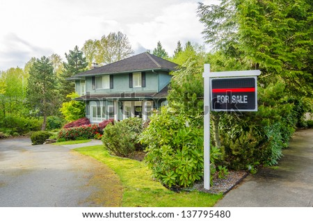 House For Sale Real Estate Sign in Front of a House. - stock photo