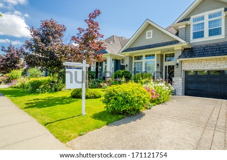 House For Sale. Real Estate Sign in Front of a House. - stock photo