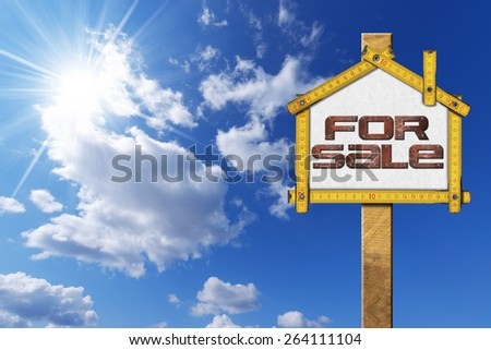 House For Sale Sign - Wooden Meter. Yellow wooden meter ruler in the shape of house with text for sale. For sale real estate sign on blue sky with cloud and sun rays - stock photo