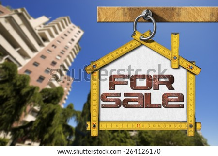 House For Sale Sign - Wooden Meter. Yellow wooden meter ruler in the shape of house with text for sale. For sale real estate sign with tall and blurred buildings in the background - stock photo