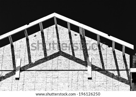 house frame construction and shadows at a construction site - stock photo