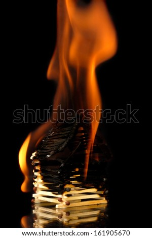 House from matches burning down with flames. Conceptual symbol isolated on black background - stock photo