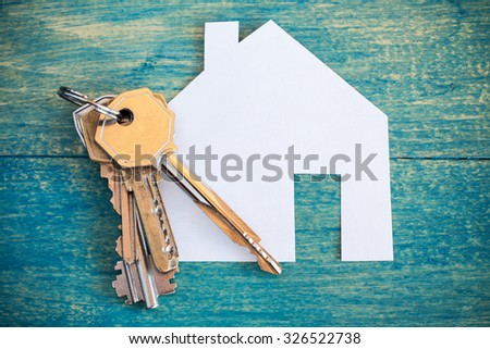 House icon and keys on wooden background - stock photo
