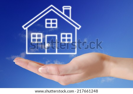 House in hand over blue sky concept  - stock photo