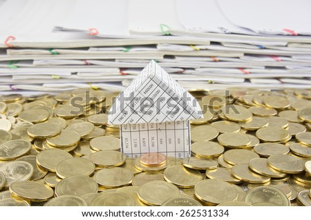 House in heap of gold coins  with pile of paperwork as background. - stock photo