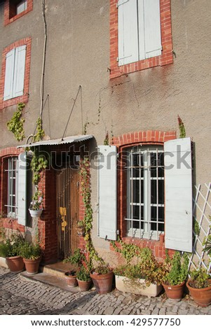 House in Provencal style with wooden shutters and a plastered facade - stock photo