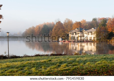 house in the autumn forest on the shore of the lake is reflected in the water