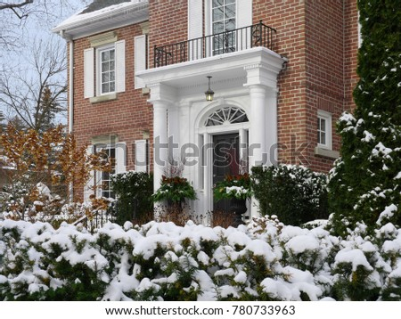 house in winter with snow covered shrubs