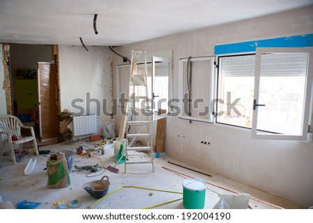 House indoor improvements in a messy room construction with plaste tools and ladder - stock photo