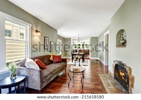 House interior in soft mint color with hardwood floor, brown soft couch and glass top coffee table