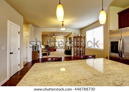 House interior with Open floor plan. Kitchen interior with hardwood floor and Cozy living room in light tones. - stock photo