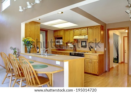 House interior with open floor plan. Kitchen with maple cabinets and bar counter