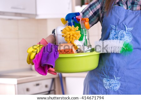 House keeper holding basin full of cleaning supplies in front of clean kitchen - stock photo