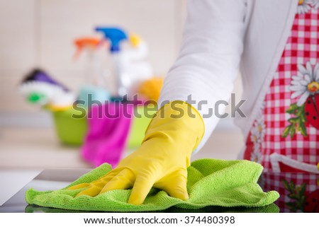 House keeper wiping glass table with cloth. Cleaning supplies in washbasin in background - stock photo