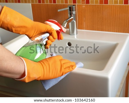 House keeping: cleaning bathroom sink with spray - stock photo