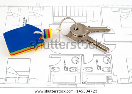 House key on blueprints with an architecture model in the background