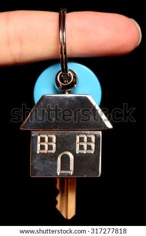 House keyring and key on black background - stock photo