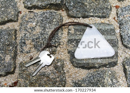 house keys and Keychain on stone background