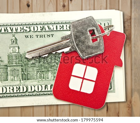 House keys and the hundred dollar banknotes on wooden table - stock photo
