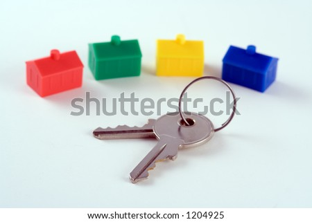 House keys in front of a row of plastic houses