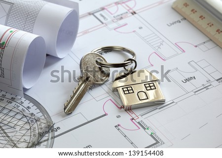 House keys on a house plan blueprint concept for new house design or home improvement - stock photo