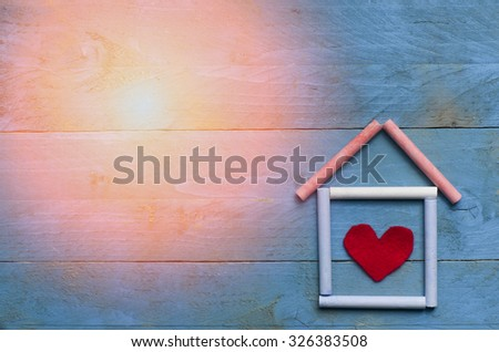 House made of chalk with red heart in on blue wooden background. Sun in a corner. - stock photo