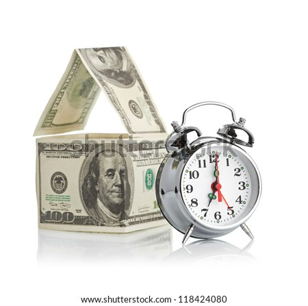 house made of dollars and alarm clock. Isolated on white background. - stock photo