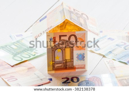 House made of Euro banknotes on a white wooden floor