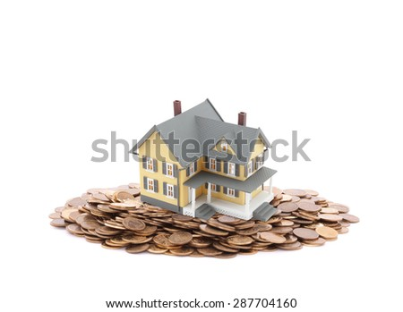 House miniature with pile of coins - stock photo