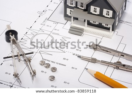 House model and drafting tools on a construction plan.