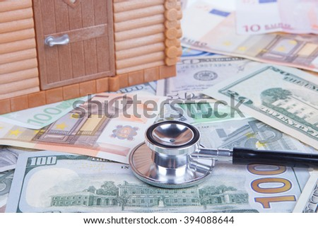 House model on money banknote with stethoscope - stock photo