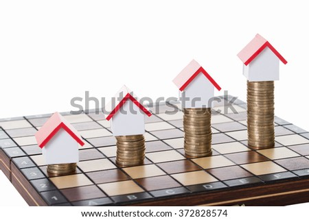 House models and stacked coins on chessboard against white background
