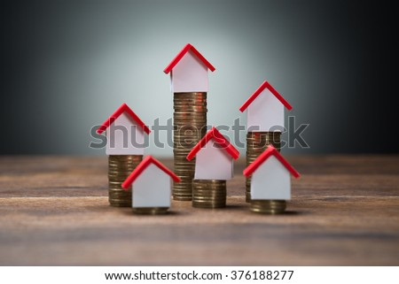 House models on stacked coins at wooden table