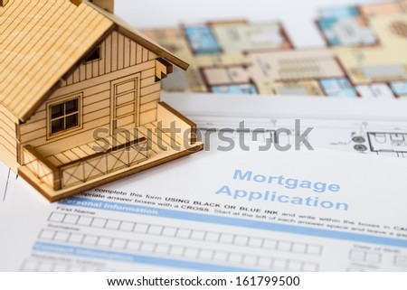 House mortgage application with model house and construction plan - stock photo